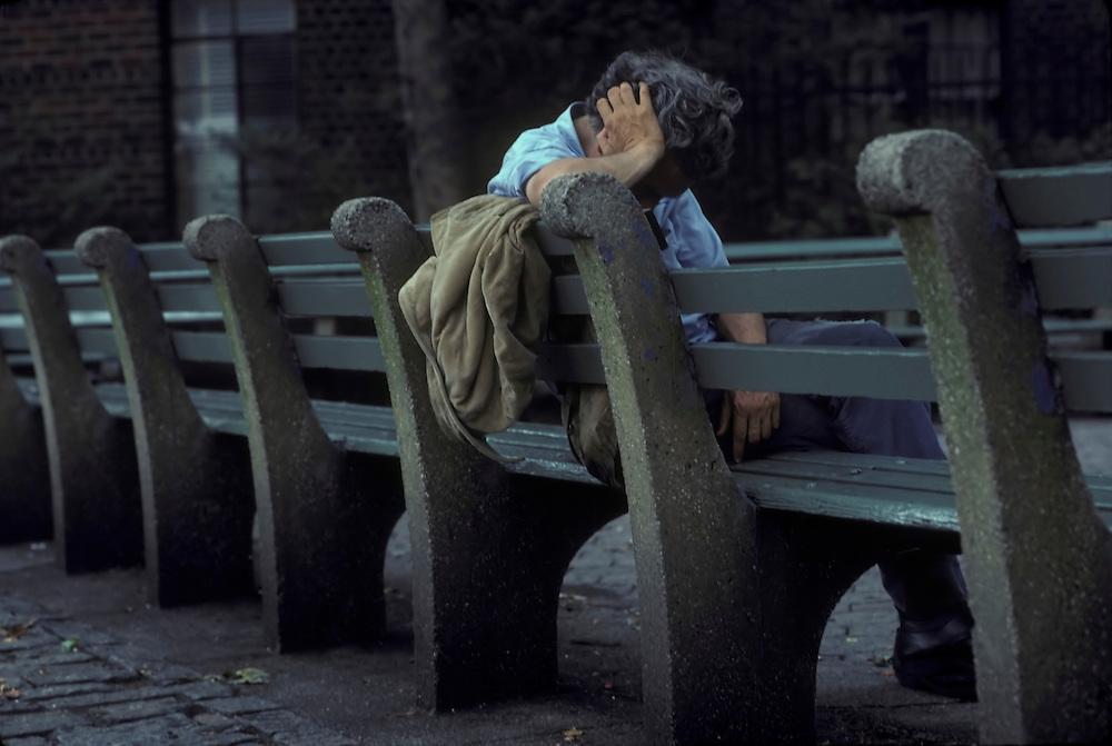 Homeless man sleeping on a park bench, Greenwich Village, New York City