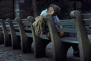 Homeless man sleeping on a park bench, Greenwich Village, New York City