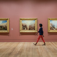 London, UK - 8 September 2014: a gallery assistant walks past Turner's three final masterpieces shown in newly reconstructed frames: Mercury Sent to Admonish Aeneas, The Visit to the Tomb and The Departure of the Fleet c.1850 during the press preview of The EY Exhibition: Late Turner – Painting Set Free exhibition at Tate Britain