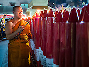 "07 FEBRUARY 2016 - BANGKOK, THAILAND: A Buddhist monk lights candles during a Chinese New Year ceremony at Wat Traimit in Bangkok's Chinatown neighborhood. Chinese New Year, also called Lunar New Year or Tet (in Vietnamese communities) starts Monday February 8. The coming year will be the ""Year of the Monkey."" Thailand has the largest overseas Chinese population in the world; about 14 percent of Thais are of Chinese ancestry and some Chinese holidays, especially Chinese New Year, are widely celebrated in Thailand.        PHOTO BY JACK KURTZ"