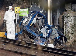 © Licensed to London News Pictures. 17/02/2018. Horsham, UK. A policeman in protective overalls stands next to the remains of a car which was hit by a train near a level crossing after two people were killed near the village of Barns Green. Photo credit: Peter Macdiarmid/LNP