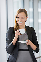 Beautiful businesswoman drinking coffee in office