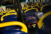 Taxi and other traffic with yellow seating handles from the top deck of a London double-decker bus.