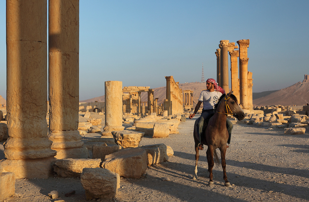 Young Syrian on his horse in  ancient Palmyra, Syria. Palmyra was an important city of central Syria, located in an oasis 215 km northeast of Damascus and 180 km southwest of the Euphrates river. It had long been a vital caravan city for travelers crossing the Syrian desert and was known as the Bride of the Desert.