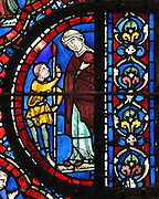 Man talking to a giant, from the causes of the flood, from the Life of Noah stained glass window, 13th century, in the nave of Chartres cathedral, Eure-et-Loir, France. Chartres cathedral was built 1194-1250 and is a fine example of Gothic architecture. Most of its windows date from 1205-40 although a few earlier 12th century examples are also intact. It was declared a UNESCO World Heritage Site in 1979. Picture by Manuel Cohen