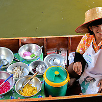 Merchant in Boat at Taling Chan Floating Market near Bangkok, Thailand <br />