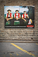 Photo of a large poster advertisement of men in traditional swiss clothing for Appenzeller cheese on the side of a building in Appenzell, Switzerland