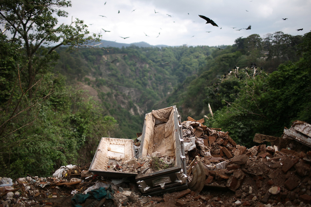 After cemetery workers exhumed a skeleton of  a man whose family did not pay the cemetery fees, the empty coffin is seen at the edge of a cliff, in Guatemala City, May 20, 2009. Every year, over 2000  graveyards of individuals are exhumed after their relatives have not paid the cemetery fees. According to the main cemetery rules, six years after the burial, relatives must pay 180 Quetzales -around $24- to renew the graveyard permission for another period of 4 years.  After sending a telegram, if there is no payment, cemetery workers destroy the individual  graveyards, and throw the skeletons into a collective graveyard (AP Photo/Rodrigo Abd)