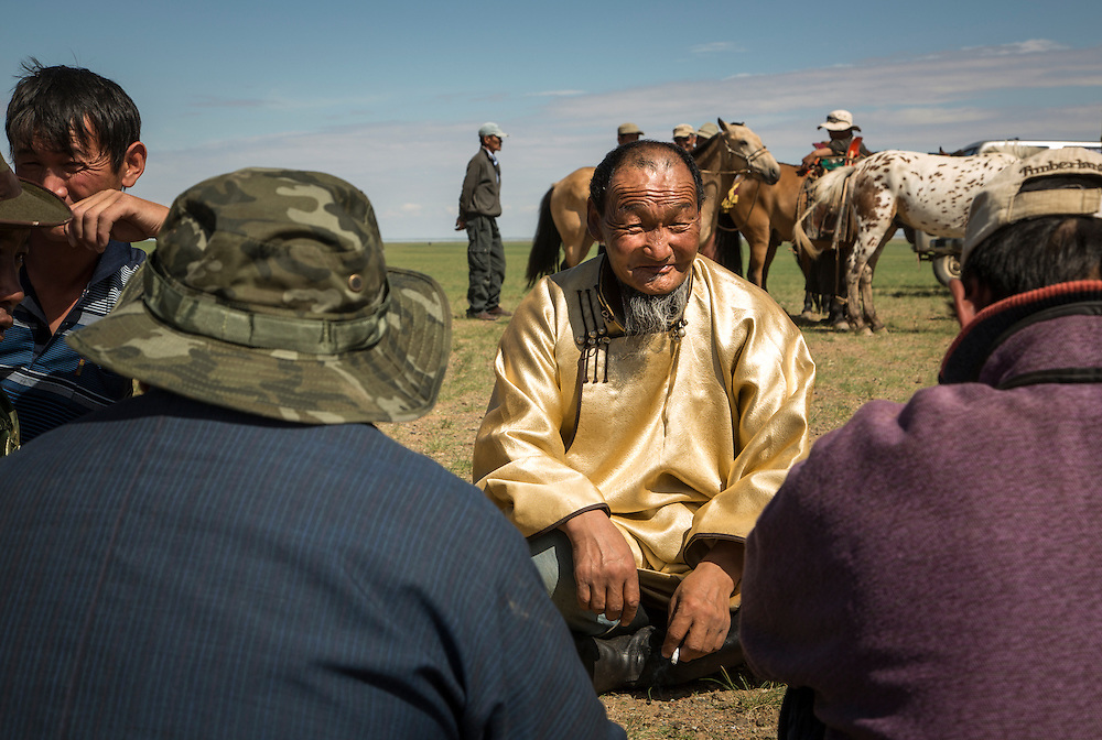 Mongolian men sit in a circle talking prior to the start a Naadam Festival at the Three Camel Lodge in the Gobi Desert of Mongolia on July 31, 2012. © 2012 Tom Turner Photography.