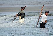"A North Korean couple pull a fishing net through water in the town of Sinuiju July 8, 2006. China and North Korea are separated by the Yalu River, upon which Chinese tourists take pleaure cruises across the water to  observe their less economically developed neighbors.  North Korea has threatened to take ""stronger physical actions"" after Japan imposed punitive measures in response to its barrage of missile tests and pushed for international sanctions. North Korea has vowed to carry out more launches and has said it will use force if the international community tries to stop it. DPRK, north korea, china, dandong, border, liaoning, democratic, people's, rebiblic, of, korea, nuclear, test, rice, japan, arms, race, weapons, stalinist, communist, kin jong il"