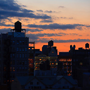 Looking west from the Bowery at sunset, rooftop water tanks, Manhattan, New York, NY