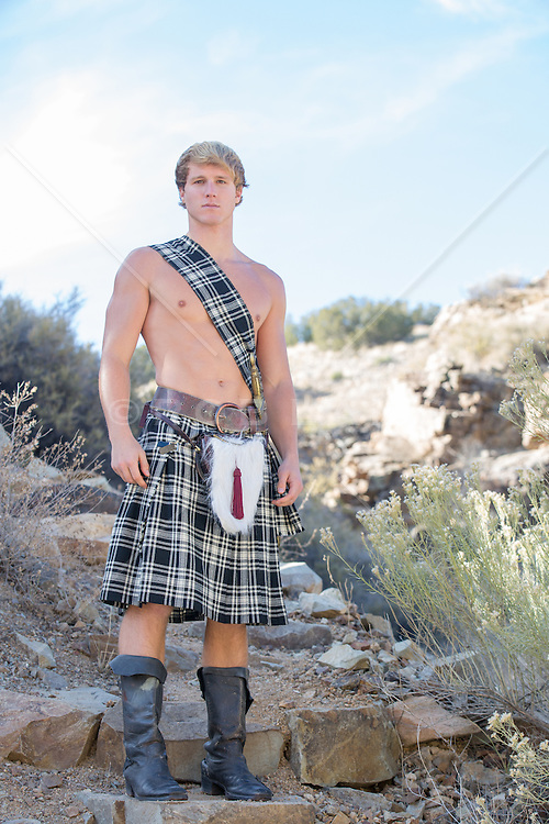 sexy blond man in a kilt outdoors