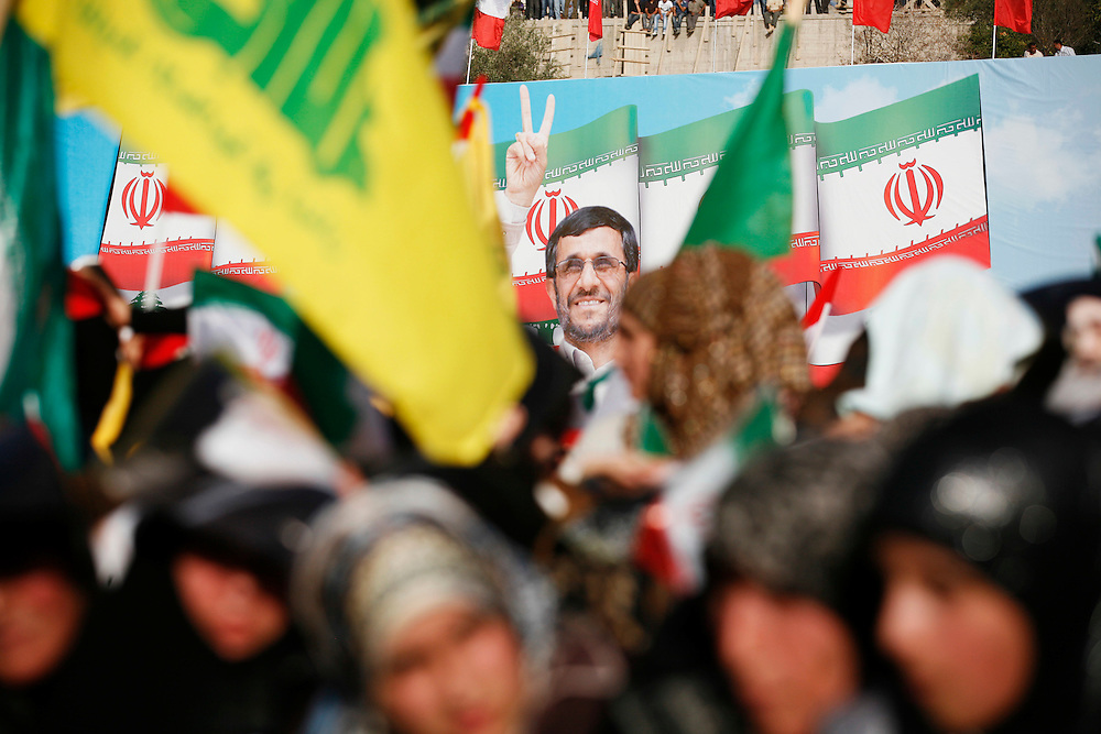 On the second and final day of his visit to Lebanon, Iranian President Mahmoud Ahmadinejad traveled to the southern town of Bint Jbeil. There a Hizballah-organized rally was held to welcome Ahmadinejad to the south Lebanon, an area where Hizballah is widely supported. Tens of thousands gathered for hours holding flags of Iran, Hizballah, Lebanon and other political parties, cheering the Iranian president as he arrived by helicopter from Beirut. ///People rally in front of a sign at the stadium in Bint Jbeil shows Iranian President Mahmoud Ahmadinejad.