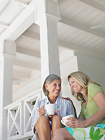 Two women holding coffee mugs sitting on verandah low angle view
