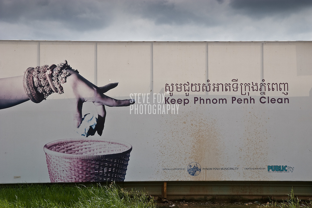 "A public information billboard saying ""Keep Phnom Penh Clean"" and show the hand of a traditional Khmer dancer placing rubbish in bin."