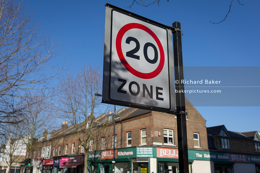 A 20mph speed limit signpost and local shops on Lordship Lane, in East Dulwich, on 15th March 2017, London borough of Southwark, England.