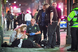 © Licensed to London News Pictures . 30/10/2016 . Manchester , UK . A paramedic tends to a woman lying on the pavement on Portland Street . Revellers on a night out , many in fancy dress , on the weekend before Halloween . Photo credit : Joel Goodman/LNP