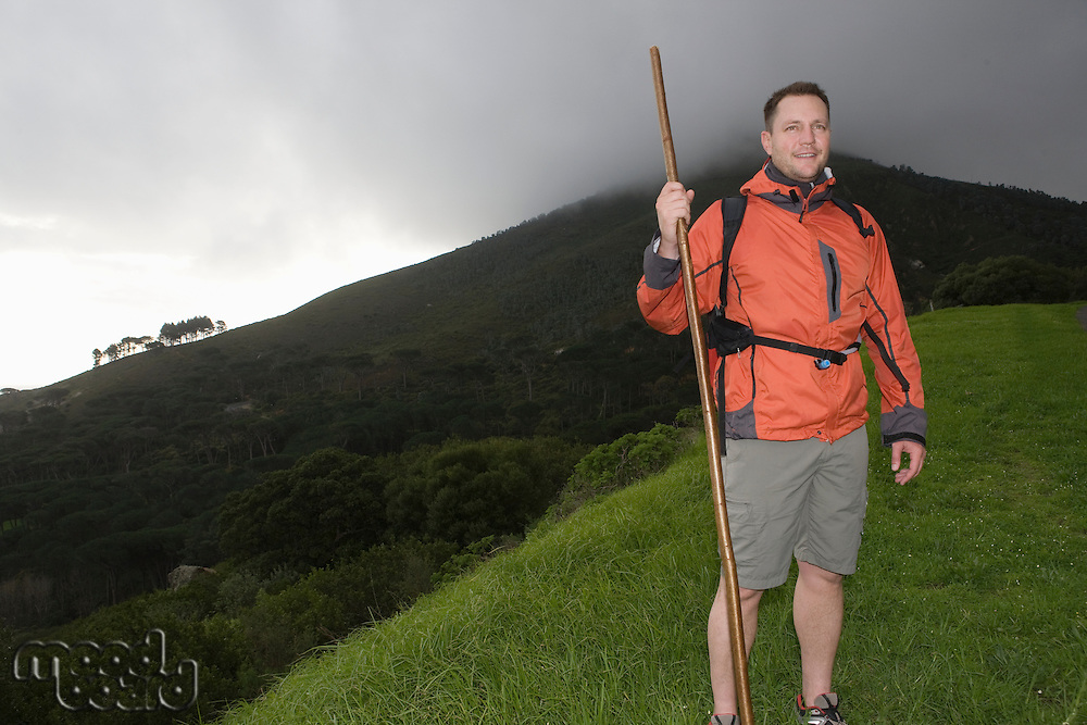 Middle-aged man stands on hillside in waterproof clothing