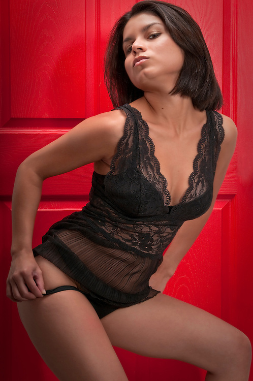 Young and sexy model posing very sexy in front of red door.