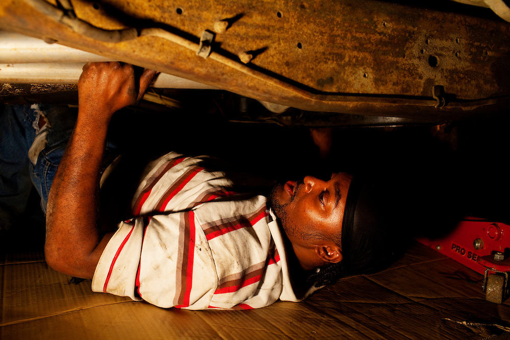 Nehemiah Hawkins works late at night to repair a car at his father's auto shop, just over the tracks from the Baptist Town neighborhood of Greenwood, Mississippi on February 16, 2011. Obstructed by his arm is a handgun, tucked into his pants for safety.