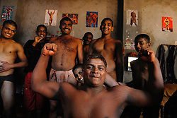 "KOLHAPUR, INDIA - MARCH 22: Indian men practice the three thousand year old sport known as ""Kushti"", a form of wrestling, in its traditional form at the fight club Shahupuri in Kolhapur, India.  In this south-eastern Indian city Kushti has a long tradition. It used to be supported by local maharajas and is financed by the government. But its days are numbered. Last year, the Indian Fighters Federation in the capital of New Delhi stunned thousands of fighters when it announced prohibition of fighting on red soil and ordered fight clubs to buy mattresses for their arenas. Ending the traditional red clay wrestling was an idea sprouted from the aspiration to achieve more Olympic medals since the last and only medal India brought home in wrestling was a bronze in 1952. So far no one here in Kolhapur is buying the mattresses and instead they continue the rigorous schedule of waking up at 3:30am six times a week and practicing more than 6 hours every day. They live together in one small room above the arena and their only belongings are a blanket, a few items of clothes and some books about the art of Kushti. They have been compared to holy men because of their celibacy and dedication and they practice exercises like standing on one's head for lengths of time to expel ""filthy"" thoughts. (Photo by Ami Vitale)"
