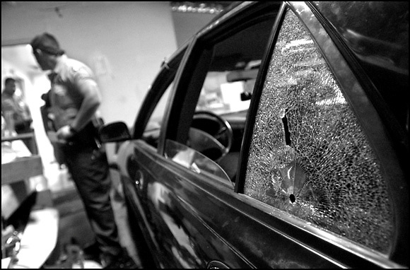 Michael Stenerson / Staff Photographer.Bullet holes mark the rear window of a car that was involved in a shooting Thursday eveing in Victorville. Deputy Gary Scheidemantle inspects the garage housing the vehicle as officers question the residents.