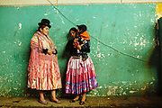 "Maria Eugenia Herrera Mamani, alias ""Claudina the Cursed"", talks with Sarita, alias ""The Romantic"", before start the wrestling's show in a Community Center El Alto. The Cholitas wear the traditional costumes of Aymara people during wrestling shows, Bolivia, February 26, 2012. <br /> SPANISH: Maria Eugenia Herrera Mamani alias Claudina La Maldita  talks to Sarita alias La Romantica before starting the wrestling's show in a Community Center El Alto. The Cholitas when go into the ring to wrestle wear the traditional costumes of Aymara people, El Alto, Bolivia, February 26, 2012."