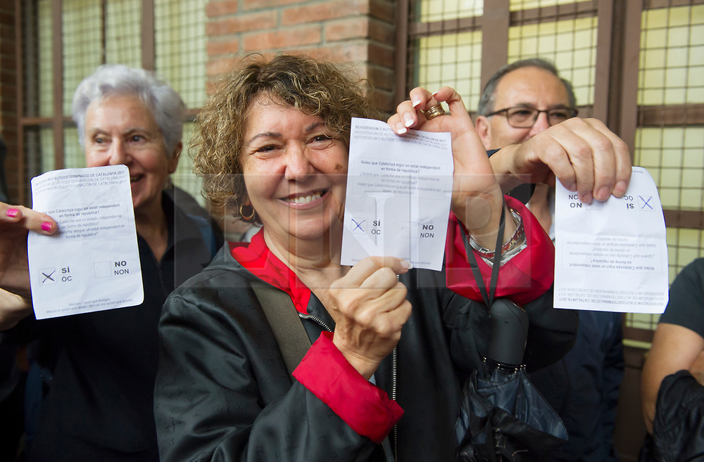 """© Licensed to London News Pictures. 01/10/2017. Barcelona, Spain.  <br /> <br /> A woman shows her vote before votting at Sedeta de Gracia´s Centre Civic.<br /> <br /> Students, their parents, associations and neighbours have organized to carry out """"playful activities"""" during the weekend and keep open the Sedeta de Gracia´s Centre Civic.<br />  <br /> Since early in the morning dozens of people wait at the college´s door for the voting time under the rain.<br /> <br /> Mossos d´Escuadra said they won´t do nothing if that can destabilize social order.<br /> <br /> Catalonia is awaiting for today, October 1st, when the Spanish Region wants to vote in a self-determination referendum to get a independence.<br /> <br /> The Referendum´s Law was passed on last September 6th at the Catalonian Parliament thanks to the votes of """"Junts pel Sí"""" and """"CUP"""". Then it was suspended by the Spanish Constitutional Court, on next day.<br /> Carles Puigdemont, the President of the Government ofCatalonia, said he would ignore that and he and his Government will continue with the Referendum.<br /> <br /> The Spanish Government has sent to Catalonia thousands of """"Guardia Civil"""" and """"Policía Nacional"""" officers (two of the Spanish forces and state security forces), to enforce the ruling of the Constitutional Court and avoid the voting process on next Sunday. They will work with the Mossos d´Escuadra (the Autonomic police in Catalonia).<br /> <br /> To avoid the vote, the Spanish Government has prevented the opening of polling stations, some of which are schools.  <br /> <br /> Photo credit: Gustavo Valiente/LNP"""