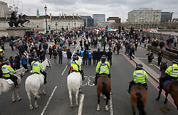 © Licensed to London News Pictures .29/03/2017.London, UK. Mounted police stand guard as people gather on Westminster Bridge at exactly one week since Khalid Masood's terrorist attack. Flowers were placed to remember the lives of those killed in the attack on the bridge and at the entrance to Parliament on 22nd March 2017.Photo credit: Peter Macdiarmid/LNP