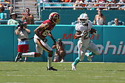 Sunday, October 13, 2019; Miami Gardens, FL USA;  Miami Dolphins running back Mark Walton (22) runs with the ball while Washington Redskins cornerback Quinton Dunbar (23) prepares to tackle during an NFL game at Hard Rock Stadium. The Redskins beat the Dolphins 17-16. (Kim Hukari/Image of Sport)