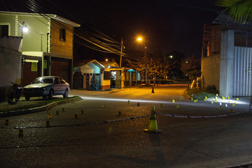 San Pedro Sula, Honduras<br /> <br /> Mirna Aracely Sanches, vd f&ouml;r en s&auml;kerhetsfirma blir avr&auml;ttad p&aring; &ouml;ppengata.<br /> Nyfikna i omr&aring;det stannar till f&ouml;r att se p&aring; n&auml;r polisen g&ouml;r sin tekniska unders&ouml;kning.<br /> <br /> Photo: Niclas Hammarstr&ouml;m