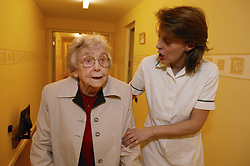 Carer helping an elderly woman walking along a corridor in sheltered accommodation,