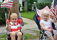 A young boy and girl in strollers and waving American Flags watch the Memorial Day Parade on Monday, May 28, 2012, in Merrick, New York, USA. America's war heroes are honored on this National Holiday.