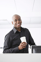 Office worker holding coffee cup in office