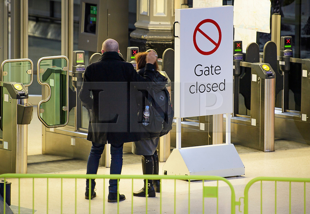 © Licensed to London News Pictures. 14/12/2016. London, UK. A couple stand at a closed gate during rush hour at Victoria Station on 14 December 2016, as hundreds of thousands of rail passengers face a second day of a 3 day all-out strike in an escalating dispute over the role of conductors between Southern Rail and the RMT Union. Photo credit: Ben Cawthra/LNP