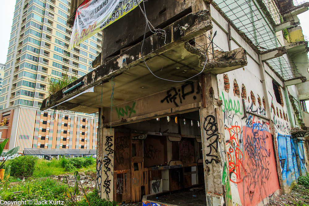 16 OCTOBER 2012 - BANGKOK, THAILAND:  An abandoned building on Phetchaburi Rd in central Bangkok, Thailand. The building sits in an empty lot next to an exclusive high rise condominium building. It used to be an optician's shop with residences above the ground floor shop. The global economic slowdown had little visible effect in Bangkok. Construction projects dot the city of 12 million and development continues unabated.   PHOTO BY JACK KURTZ