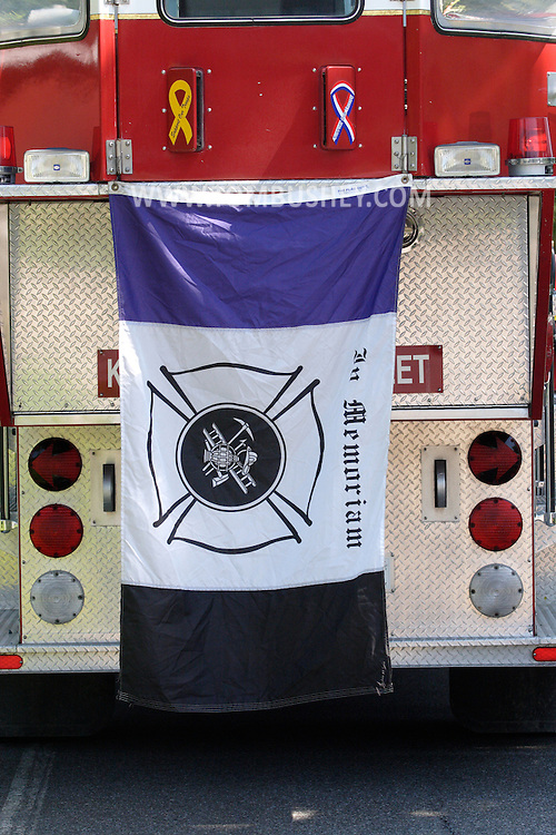 Middletown, NY - A flag hangs from the rear of a fire truck during services for Donald H. Kimble Jr., a former chief of the Middletown Fire Department, on Aug. 11, 2007.