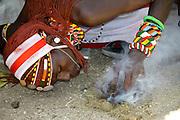 Kenya, Masai Mara, Masai (Also Maasai) Tribesmen an ethnic group of semi-nomadic people. Warriors with traditional headdress and ochre lights a fire