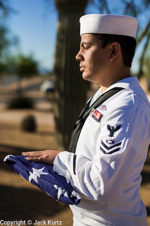 08 OCTOBER 2013 - PHOENIX, AZ:    A member of the US Navy holds an American flag during a ceremony honoring the unclaimed remains of US military veterans at the National Memorial Cemetery in Phoenix. The cremated remains of 36 unclaimed US military veterans were interred at the National Memorial Cemetery in Phoenix. Members of the US military and several hundred veterans of the US military attended the service, which was a part of the Missing In America Project (MIAP).   PHOTO BY JACK KURTZ