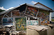 A decaying house is mended with paintings which depict daily life in Vietnam, Nha Trang, Khanh Hoa Province, Vietnam, Southeast Asia