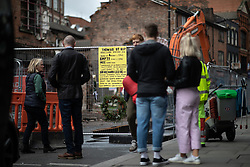 © Licensed to London News Pictures . 06/10/2018. Manchester , UK . A wreath and a single white rose are fixed to fencing beside a hand-drawn placard bemoaning the loss of a part-demolished building on the corner of Thomas Street and John Street , which criticises Manchester City Council leader Sir Richard Leese . The building is reported to have become dangerous following heavy rains after years of neglect . Campaigners say that the architectural heritage of the Northern Quarter of Manchester City Centre is under threat from developers and Manchester City Council planning policy . Photo credit : Joel Goodman/LNP