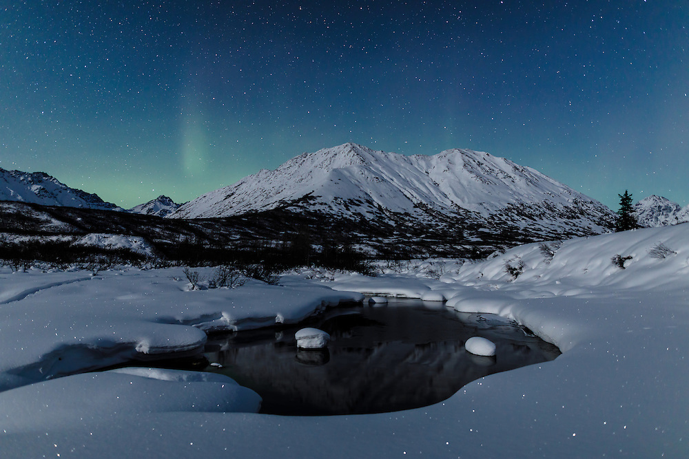 Aurora Borealis (Northern Lights) dance above Idaho Peak and the Little Susitna River at Hatcher Pass in Southcentral Alaska. Winter.