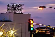 Pomona Avenue traffic signal (all signals lit) with Fox Fullerton theatre marquee and pink/violet sunset sky as backdrop. Fullerton, California.