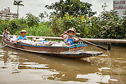 "17 NOVEMBER 2012 - BANGKOK, THAILAND:  Women paddle their canoe to a nearby market in the Thonburi section of Bangkok. Bangkok used to be known as the ""Venice of the East"" because of the number of waterways the criss crossed the city. Now most of the waterways have been filled in but boats and ships still play an important role in daily life in Bangkok. Thousands of people commute to work daily on the Chao Phraya Express Boats and fast boats that ply Khlong Saen Saeb or use boats to get around on the canals on the Thonburi side of the river. Boats are used to haul commodities through the city to deep water ports for export.    PHOTO BY JACK KURTZ"