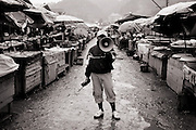 A UXO Lao de-mining technician clears the market area of Sam Neua, northern Laos, in preparation for a controlled explosion.