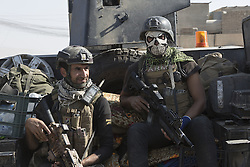 October 23, 2016 - Bartella, Nineveh, Iraq - Two Iraqi Army counter terrorism soldiers travel on the back of an armoured Humvee in the recently captured Iraqi town of Bartella...Bartella, a mainly Christian town with a population of around 30,000 people before being taken by the Islamic State in August 2014, was captured two days ago by the Iraqi Army's Counter Terrorism force as part of the ongoing offensive to retake Mosul. Although ISIS militants were pushed back a large amount of improvised explosive devices are still being found in the town's buildings. (Credit Image: © Matt Cetti-Roberts/London News Pictures via ZUMA Wire)