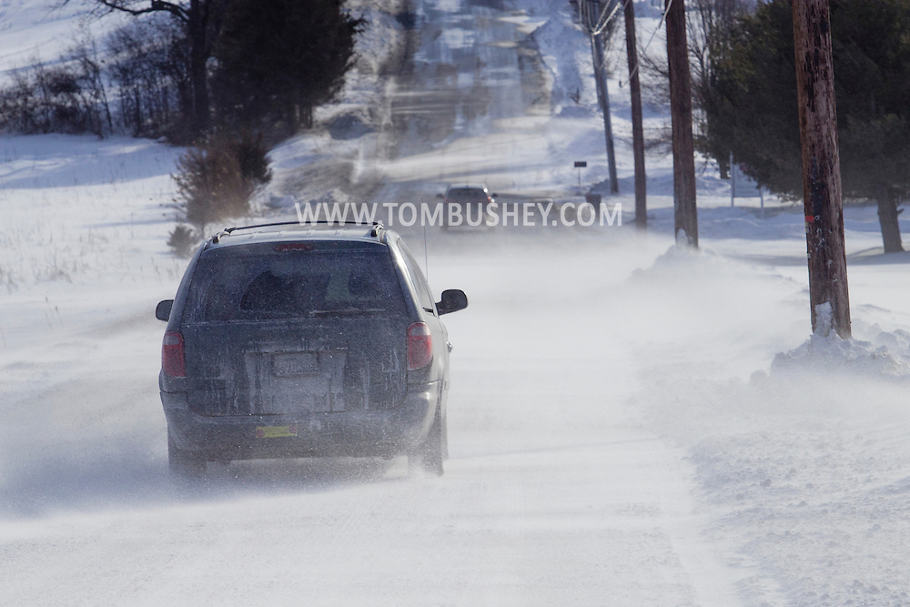 Chester, New York - Strong winds blow snow across Black Meadow Road as cars drive through on Feb. 19, 2015. ©Tom Bushey / The Image Works