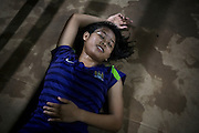 Phatsorn Bunmasen, 14, is relaxing on the floor the gym where she practises Muay Thai boxing, in a village near Ubon Ratchathani, northeast Thailand.