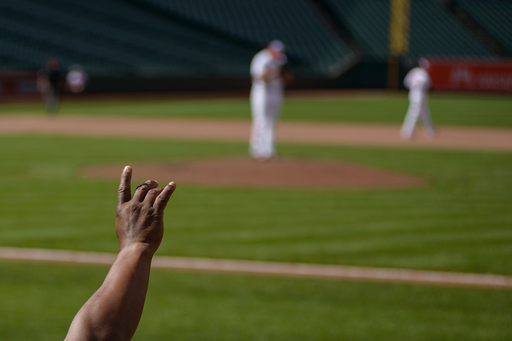 Baltimore, MD - April 29, 2015: Orioles first base coach Wayne Kirby signals two outs against the White Sox at the top of the 9th inning from the Oriole's dugout at an empty Oriole Park at Camden Yards on April 29, 2015. The civil unrest in Baltimore has forced the game between the Chicago White Sox and Baltimore Orioles to be closed to the public and moved to the afternoon. (Matt Roth for ESPN)