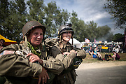 Members of the Round Canopy parachuting team walks away from the landing zone in La Fiere. Every year the group organizes jumps from original C47 planes in WWII style uniforms